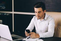 Aantrekkelijke bedrijfsmens in slimme vrijetijdskledingszitting op zijn werkende plaats die in bureau een slimme telefoon houden royalty-vrije stock foto