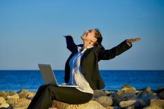 Aantrekkelijke bedrijfsvrouw die aan laptop bij strand werken stock afbeelding