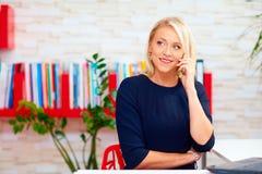 Aantrekkelijke bedrijfsvrouw die op de telefoon in bureau spreken stock afbeelding