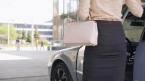 Aantrekkelijke bedrijfsvrouw die van automobiel weggaan en aan bureau lopen stock videobeelden