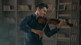 Aantrekkelijke begaafde jonge mens het spelen viool sensually De violist repeteert in de binnenlandse studio tegen stock video