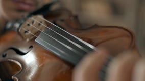 Aantrekkelijke begaafde jonge mens het spelen viool sensually De violist repeteert close-up 4K stock footage