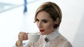 Aantrekkelijke betoverende bedrijfsvrouw in witte blouse het drinken koffie stock videobeelden