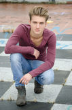 Aantrekkelijke blauwe eyed, blonde jonge mensenzitting op geruite vloer Royalty-vrije Stock Afbeeldingen