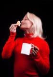 Aantrekkelijke blonde holdingskop en koekjes Stock Afbeelding