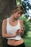 Aantrekkelijke blonde jonge vrouw die in openlucht cel gebruiken stock foto's