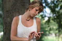 Aantrekkelijke blonde jonge vrouw die in openlucht cel gebruiken royalty-vrije stock afbeelding