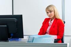 Aantrekkelijke blonde vrouw in bureauzitting Royalty-vrije Stock Foto's