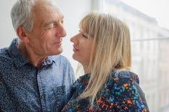 Aantrekkelijke Blonde Vrouw die de Knappe Hogere Mens koesteren en hem met Liefde en Hartstocht in Haar Ogen bekijken Paar met Le stock foto