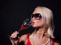 Aantrekkelijke blonde vrouw die haar cocktail drinkt Stock Afbeeldingen