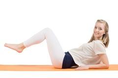Aantrekkelijke blonde vrouw opleidingsmaag, billen, heupen en benen op een mat stock foto's