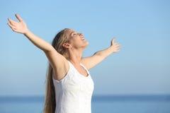 Aantrekkelijke blondevrouw ademhaling gelukkig met opgeheven wapens Royalty-vrije Stock Foto