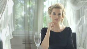 Aantrekkelijke blondevrouw die bij de restaurantlijst wachten stock video