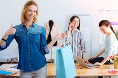 Aantrekkelijke blondevrouw die blauwe papieren zak houden royalty-vrije stock afbeeldingen