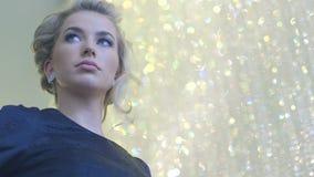 Aantrekkelijke blondevrouw die met diamantoorringen en zwarte avondjurk op somebody wachten stock footage