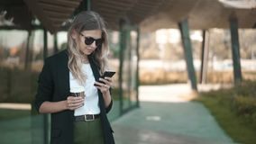 Aantrekkelijke blondevrouw die met koffie smartphone in de zomer en het glimlachen bekijken stock videobeelden