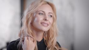 Aantrekkelijke blondevrouw die met mooi kapsel zich in een spiegel na schoonheidszittingen bekijken stock videobeelden