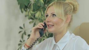 Aantrekkelijke blondevrouw die op de telefoon binnen spreken stock videobeelden