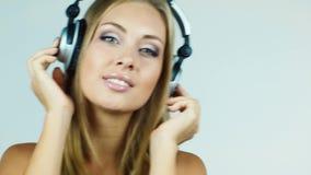 Aantrekkelijke blondevrouw die op hoofdtelefoons zetten en aan muziek luisteren stock footage