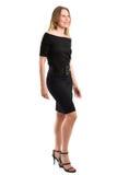 Aantrekkelijke blondevrouw in elegante zwarte die kleding, op wit wordt geïsoleerd Royalty-vrije Stock Foto's