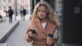 Aantrekkelijke blondevrouw met koffie die en haar smartphone lopen gebruiken stock footage