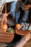 Aantrekkelijke Boheemse vrouwenzitting op een vloer met mand vruchten royalty-vrije stock foto's