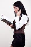 Aantrekkelijke brunette met telefoon en datebook Stock Afbeeldingen