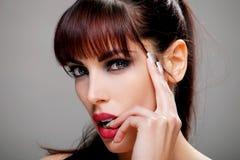 Aantrekkelijke brunette wat betreft haar lip, close-up Royalty-vrije Stock Foto