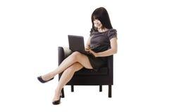 Aantrekkelijke Chinese vrouw die aan een netbook werkt. Stock Afbeelding