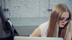Aantrekkelijke dame die aan moderne laptop in bureau werken stock footage