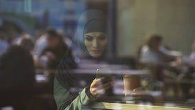 Aantrekkelijke dame die in hijab op telefoon, vrij om met vrienden te communiceren babbelen stock footage