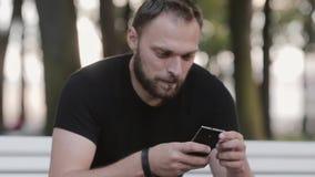 Aantrekkelijke de jonge mensenzitting van het close-upportret op een bank in het park en het gebruiken van een smartphone stock videobeelden