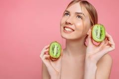 Aantrekkelijke de kiwiplakken van de meisjesholding, op een roze achtergrond Natuurlijke Schoonheid stock foto