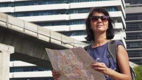 Aantrekkelijke de toeristenkaart van de vrouwenlezing op stadsstraat met scytrain bij achtergrond stock video