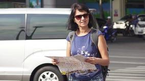 Aantrekkelijke de toeristenkaart van de vrouwenlezing op stadsstraat met zwaar verkeer bij achtergrond stock footage