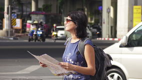 Aantrekkelijke de toeristenkaart van de vrouwenlezing op stadsstraat met zwaar verkeer bij achtergrond stock video