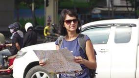 Aantrekkelijke de toeristenkaart van de vrouwenlezing op stadsstraat met zwaar verkeer bij achtergrond stock videobeelden