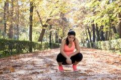 Aantrekkelijke die sportvrouw in agentsportkleding ademhaling hijgend en nemend een onderbreking en uitgeput na het runnen van tr stock foto