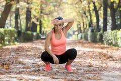 Aantrekkelijke die sportvrouw in agentsportkleding ademhaling hijgend en nemend een onderbreking en uitgeput na het runnen van tr stock fotografie