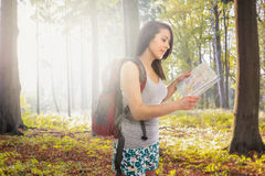 Aantrekkelijke die vrouw met rugzak in bos wordt verloren Stock Foto's