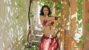 Aantrekkelijke die vrouw met tatoegeringen het dansen buikdans in gazebo met wijnstokken wordt overwoekerd stock footage