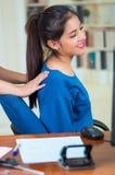 Aantrekkelijke donkerbruine bureauvrouw die blauwe sweaterzitting dragen door bureau die achtermassage, het concept van de spanni Royalty-vrije Stock Afbeelding
