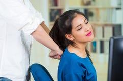 Aantrekkelijke donkerbruine bureauvrouw die blauwe sweaterzitting dragen door bureau die achtermassage, het concept van de spanni Royalty-vrije Stock Foto