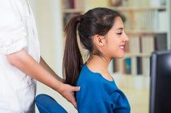Aantrekkelijke donkerbruine bureauvrouw die blauwe sweaterzitting dragen door bureau die achtermassage, het concept van de spanni Stock Afbeelding