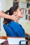Aantrekkelijke donkerbruine bureauvrouw die blauwe sweaterzitting dragen door bureau die halsmassage, het concept van de spanning Royalty-vrije Stock Foto's