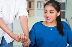 Aantrekkelijke donkerbruine bureauvrouw die blauwe sweaterzitting dragen door bureau die handmassage, het concept van de spanning Royalty-vrije Stock Afbeeldingen
