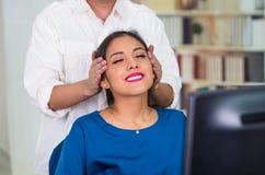 Aantrekkelijke donkerbruine bureauvrouw die blauwe sweaterzitting dragen door bureau die hoofdmassage, het concept van de spannin Royalty-vrije Stock Afbeelding