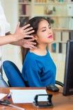 Aantrekkelijke donkerbruine bureauvrouw die blauwe sweaterzitting dragen door bureau die hoofdmassage, het concept van de spannin Royalty-vrije Stock Afbeeldingen
