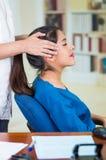 Aantrekkelijke donkerbruine bureauvrouw die blauwe sweaterzitting dragen door bureau die hoofdmassage, het concept van de spannin Royalty-vrije Stock Fotografie