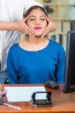 Aantrekkelijke donkerbruine bureauvrouw die blauwe sweaterzitting dragen door bureau die hoofdmassage, het concept van de spannin Stock Foto's